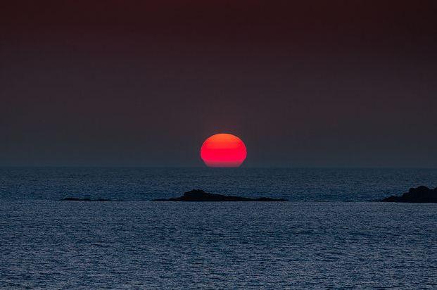Φαλάσαρνα big red globe of the sun setting into the horizon (Image by Dieter Weinelt)