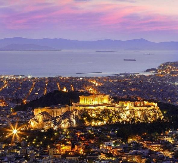 Athens at night, showing the Parthenon lit up on the Acropolis and the view to the harbour