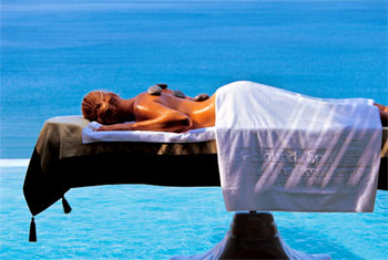 Massage client relaxing under a towel next to the sea