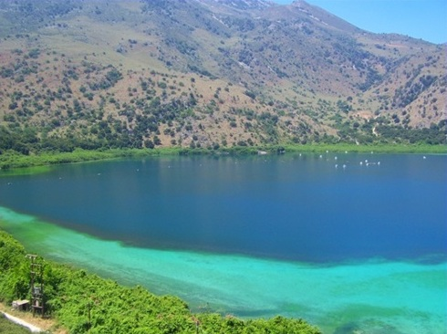 Lake Kournas - bright sand and clear waters show turquoise and blue, ringed by mountains