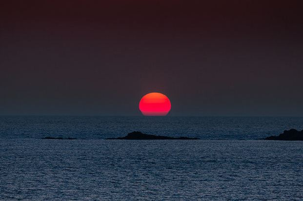 Φαλάσαρνα big red globe of the sun setting into the horizon (Image by Dieter Weinelt)