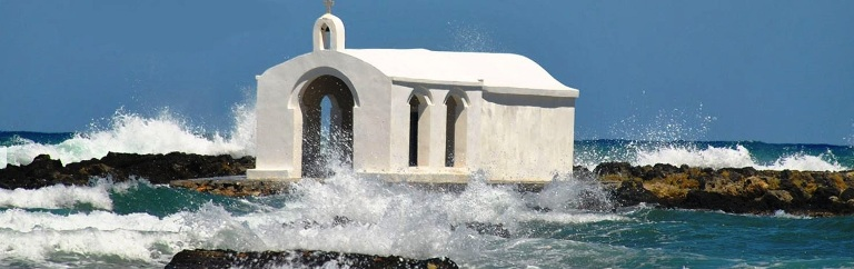The sea surrounds the chapel at Georgioupolis Beach