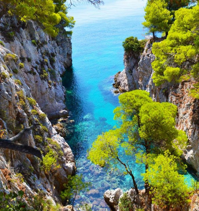 Aqua waters and treed cliffs form a miriad of colour in Skopelos