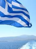 Greek Flag flying over the back of the ferry - Mediterranean blue sea