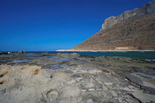 The rock pools of Stavros Beach, looking over the bay to Stavros or Vardies Mountain