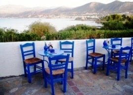 View across the Mediterranean with blue raffia chairs in the foreground cafe