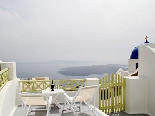 A white Santorini balcony next to a tiny chapel, with views across the bay
