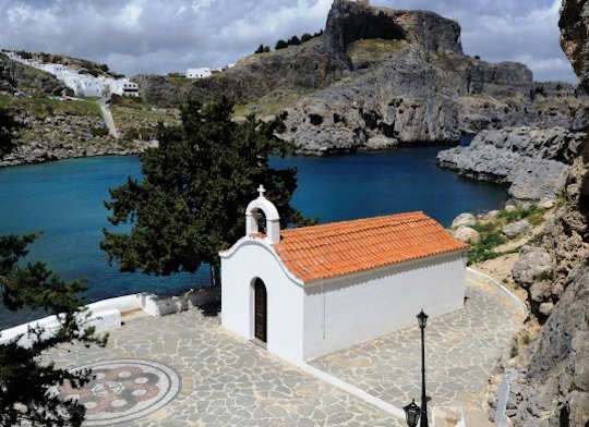 Agios Pavlos Chapel on the bay of the same name, with Lindos white village and rocky acropolis ruins behind, Rhodes