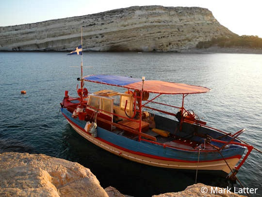 Matala bay and caves with fishing boat (image by Mark Latter)