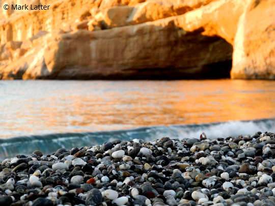 Matala Crete - the beach pebbles against the sea with the sun on the cave in the afternoon (image by Mark Latter)