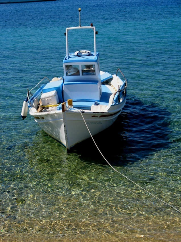 Blue and white wooden fishing boat on perfect crystal clear sea, Mykonos