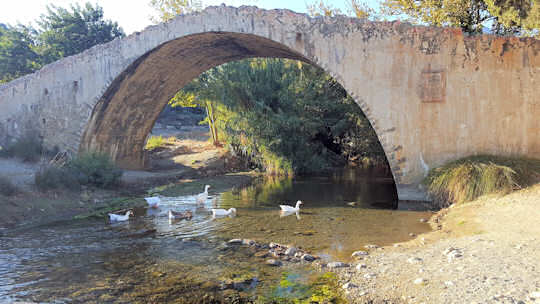 Sit by the river at the Preveli Bridge