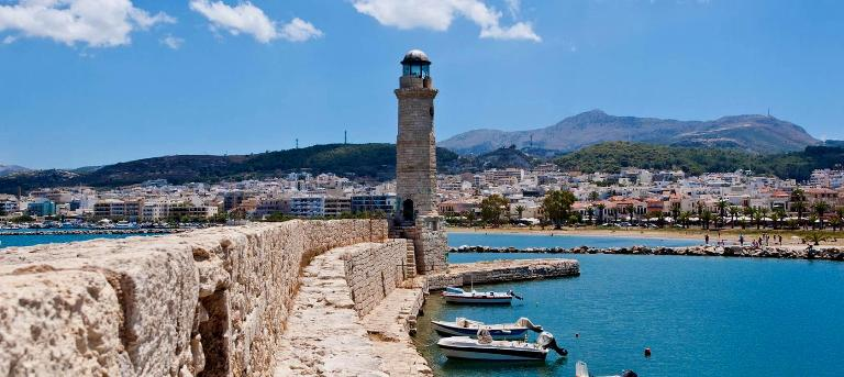 Rethymnon Crete - the walls of the old harbour with the Venetian lighthouse, looking to the west to the beach