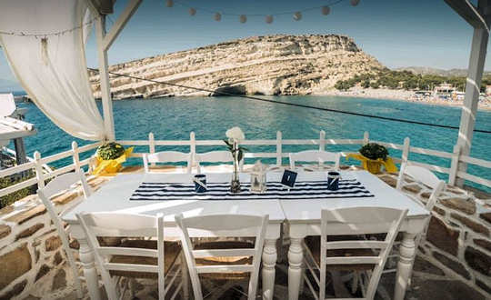 Scala fish taverna looks out across Matala Beach and over to the rocky peninsula and caves